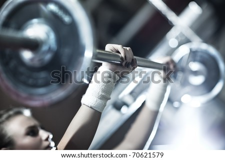 Young woman weight training Focus on hand.