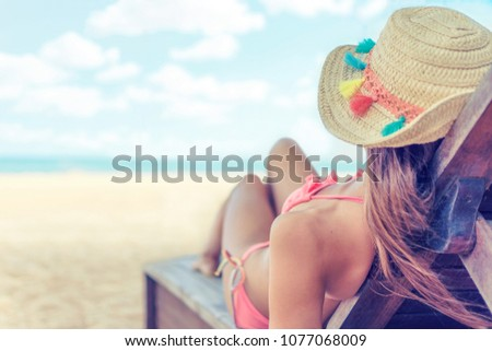 Young woman whit sun hat relaxing on sun bad enjoys sunbath at the beach with the sea and horizon in the background on hot summer day travel and tourism concept #1077068009