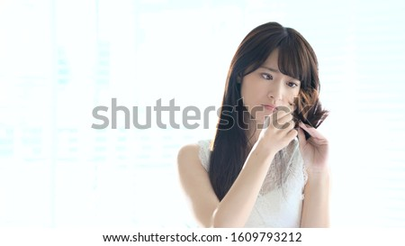 Young woman who be troubled by split ends. damaged hair. beauty and hair care concept.