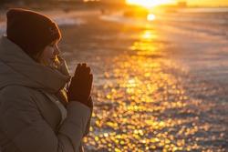 Young woman winter enjoying winter sun. Red sunset light. Winter solstice.