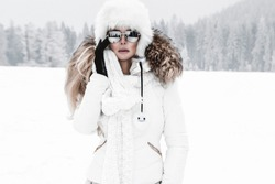 Young woman winter portrait. Winter fashion model with ski suit and goggles. Attractive young woman in wintertime outdoor. Mountains, white snow in magic winter day.