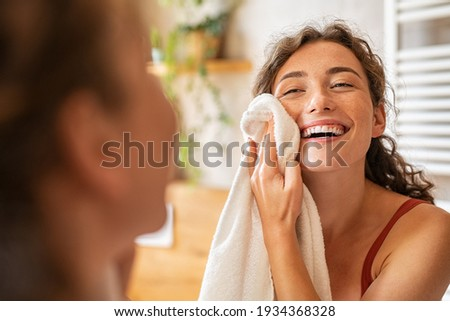 Young woman wiping her face with towel after waking up in the morning. Beautiful happy smiling girl holding towel near facial skin after washing face. Happy woman cleaning and drying skin with napkin.