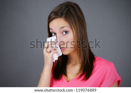 Young woman wiping her tears with a tissue or handkerchief, studio shot over grey background, great for depression, sadness or grief.