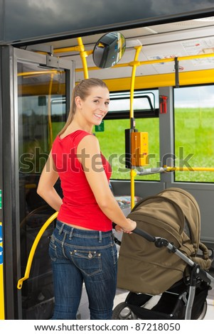 Young woman with a baby in a stroller getting into a bus on the bus station