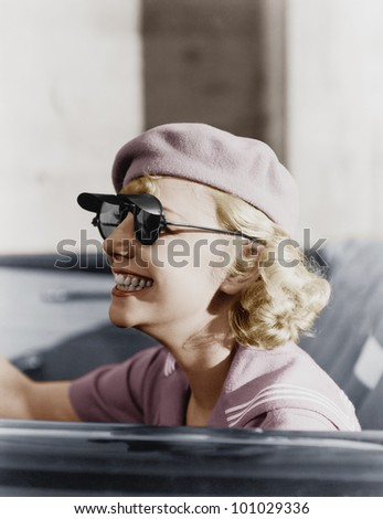 Young woman with a beret and sunglasses in a car, on the go