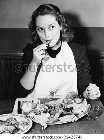 young woman with a bib eating...