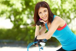 young woman with a bike in a summer park. Active people outdoors. sport lifestyle