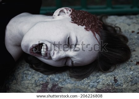 Young woman with a broken head in the blood close up