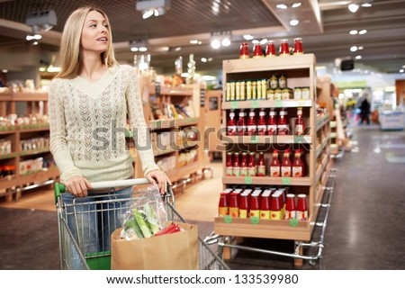 Young woman with a cart in a store