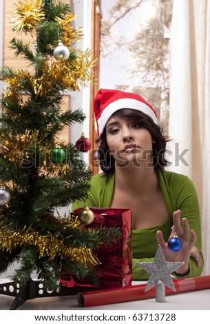Young woman with a Christmas Santa hat looking lonely in her home with her Christmas tree.
