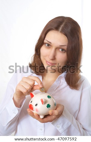 Young woman with a coin and piggy bank