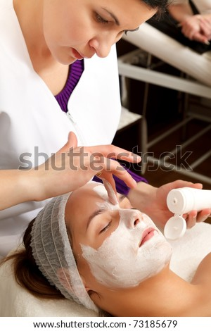 Young woman with a facial mask in a beauty salon