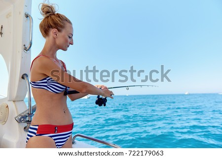 Young woman with a fishing rod fishing from the boat