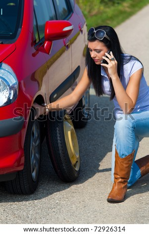 Young woman with a flat tire in car