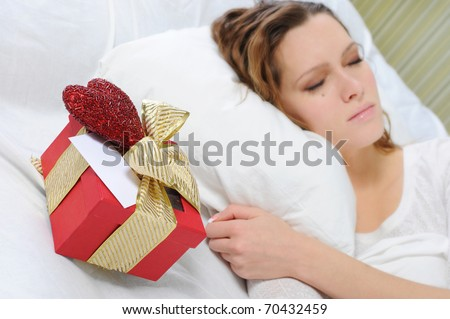 young woman with a gift box in the bed