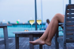Young woman with a glass of white wine at evening