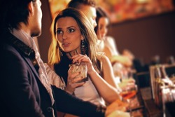 Young woman with a glass of wine talking to a man at the bar