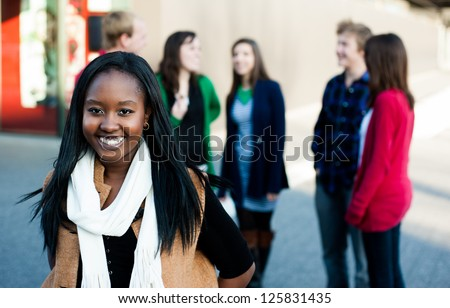 Young woman with a group of friends smiling outside