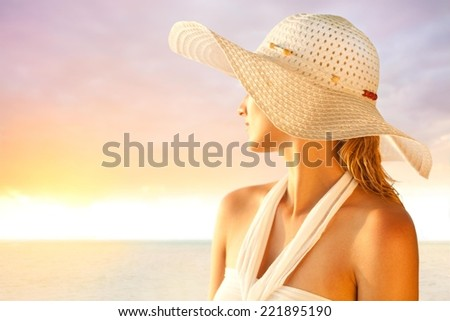 Young woman with a hat enjoying summer at the beach.