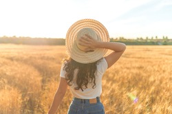 Young woman with a hat in a sunny ripe wheat field. Concept of prosperity and warmth.