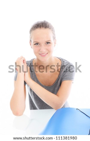 Young woman with a lovely smile sitting at a white table with a large blue folder in front of her