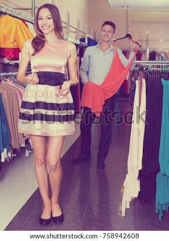 Young woman with a man trying on an elegant attire in a clothing store
