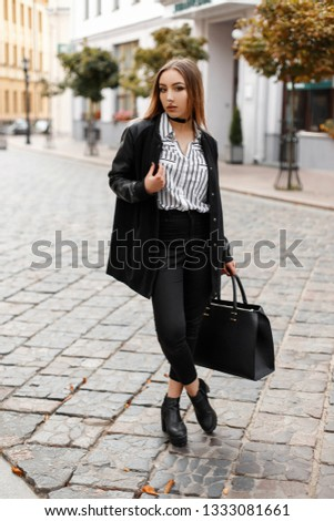 Young woman with a pierced nose in a stylish jacket in an elegant blouse in trendy jeans in a trendy leather shoes with a handbag walks along the street in the city near buildings. Cute girl. #1333081661