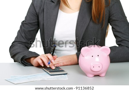 Young woman with a piggy bank and using a calculator