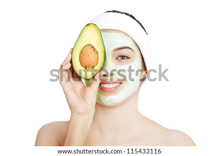 Young woman with a  smile holding avocado heaving face clay mask on the face in a spa