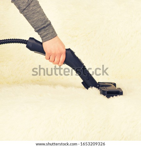 Young woman with a steam cleaner cleans the carpet on the couch - Image toned