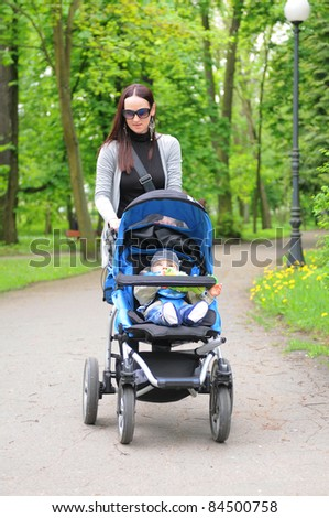 Young woman with a stroller walking in the park