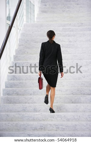 Young woman with a suitcase climbing stairs