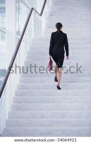 Young woman with a suitcase climbing stairs - stock photo