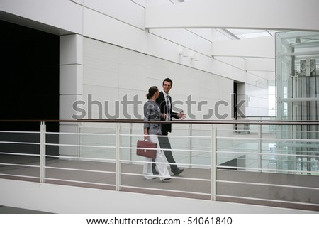 Young woman with a suitcase walking next to a young man on a gateway - stock photo