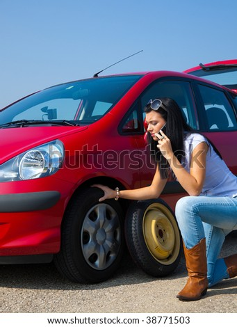 Young woman with a tire breakdown in car