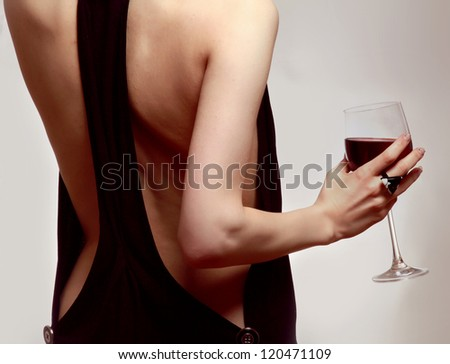 Young woman with a wineglass near the wall, isolated on grey