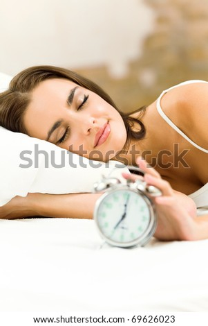 Young woman with alarmclock on the bed at the morning
