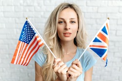 Young woman with American and British flags. Caucasian smiling girl posing with American and British flags, she stands near a white brick wall, smiling and looking at the camera