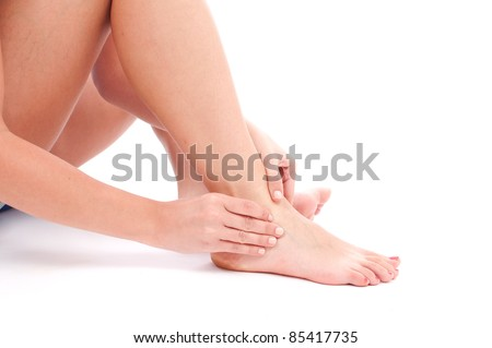 Young woman with an expression of severe pain in his leg. White background.