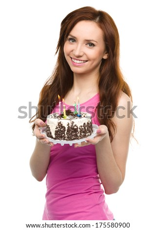 Young woman with anniversary cake, isolated over white