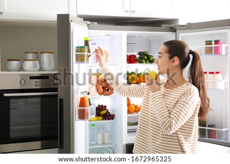 Young woman with apple near open refrigerator in kitchen