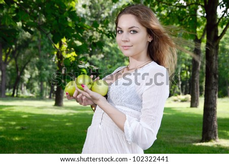 Young woman with apples in the garden