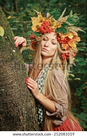 Young woman with autumn leaves in hand and fall yellow maple garden background. Woman with wreath of yellow leaves and berries on head. Autumn bright portrait sexy girl.