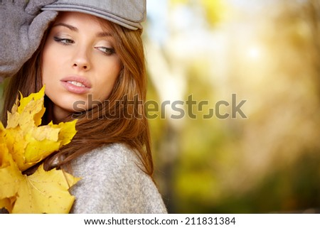 Young woman with autumn leaves in hand and fall yellow maple park  background