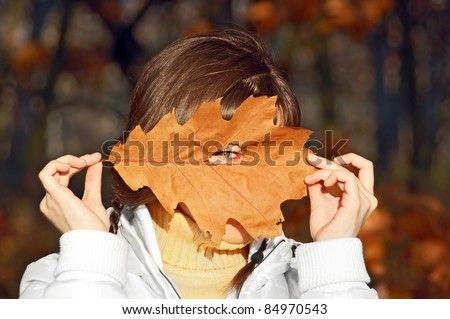 Young woman with autumn orange leaf in forest