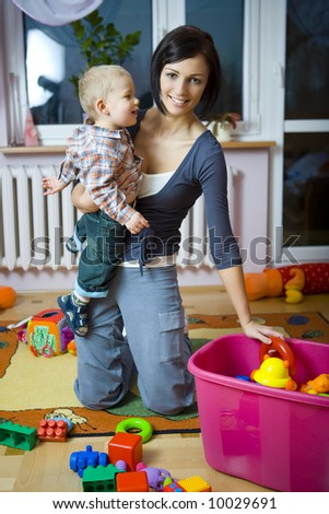 Young woman with baby boy during plaing. Woman holding baby on hand taking toy from container. Front view.