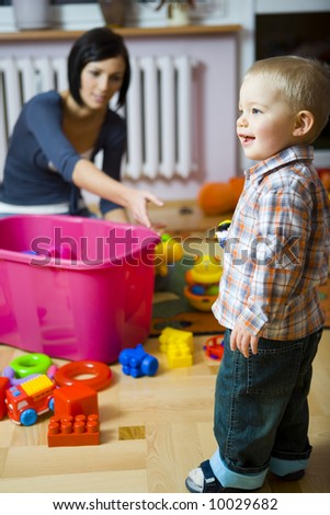 Young woman with baby boy during plaing. Woman stretches out for the toy. They are at container with toys. Focused on a boy.