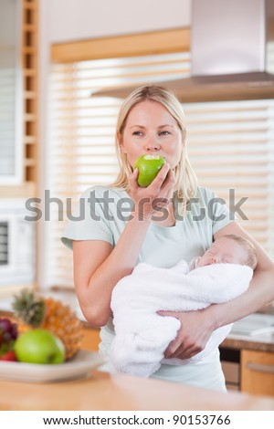 Young woman with baby on her arms having an apple