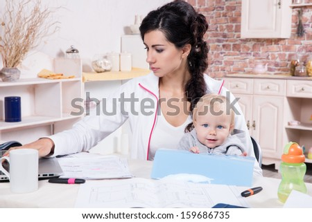 Young Woman With Baby Working From Home