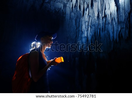 Young woman with backpack exploring cave with torch